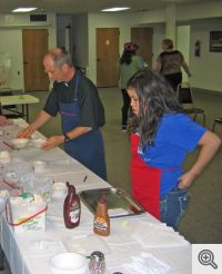 Father Bill Elser is busy serving some of his home made ice cream assisted by students from the religious education program.