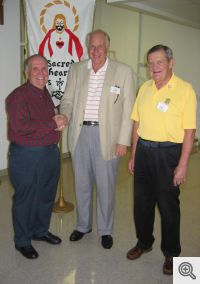 Bill Patterson (right), President of Sacred Heart Men's Club, and Buddy Dixon (left), Program Chairman, welcome John Paul to the club's October meeting.