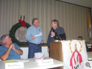 Ed Keearns, Director of the Sacred Heart Church Christmas Basket program accepts a check from Bill Patterson, President of the Men's Club, for $1200 for this program to provide Christmas gifts and food to needy area families during the week leading up to Christmas.