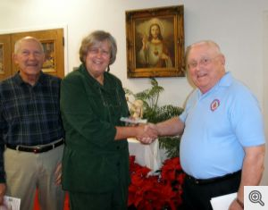 Linda Good receives Men's Club donation from Bob Heisler for Our Lady of Fatima Catholic School.