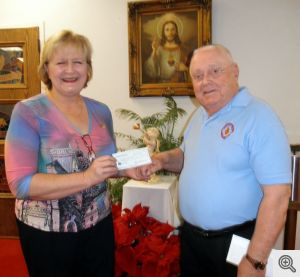 Angela Issacs accepts Men's Club donation from Bob Heisler for St. John's Catholic School.