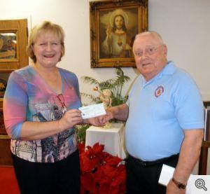 Angela Issacs accepts Men's Club donation from Bob Heisler for St. John's Catholic School.
